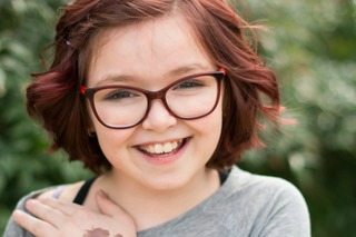 picture of young girl with reddish hair, glasses and beautiful smile
