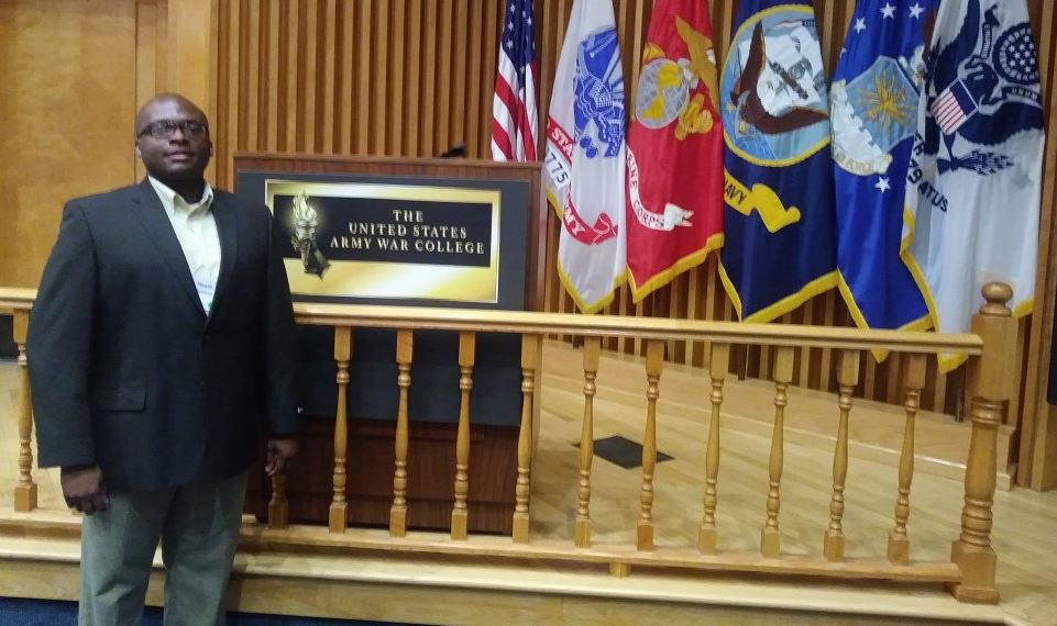 Heath stands next to a podium at the Army War college.