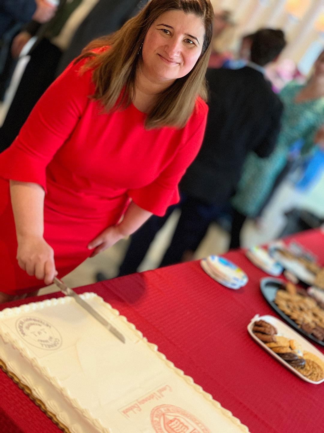 """Dr. Marta Castelhano cuts the """"accredited"""" cake at the event."""
