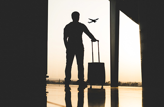 A silhouette of a man holding a suitcase inside airport