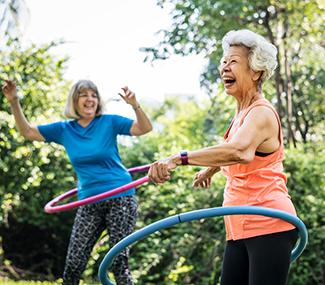 Seniors laughing using hula hoops outdoors