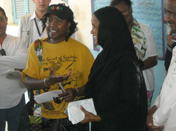 While visiting a traditional Nubian Village in Egypt, former NABSW President Dr. Gloria Batiste-Roberts presents a monetary donation to the village's school Principal.