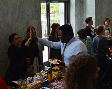 male capitol hill staff gives female naturopathic doctor a high five in the Rayburn Building during a reception