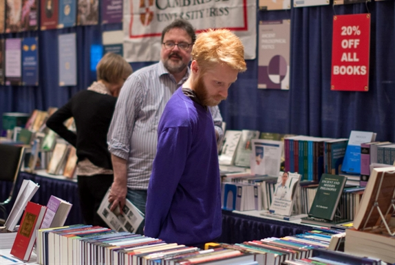 Attendees browse books in the exhibit hall at an APA meeting