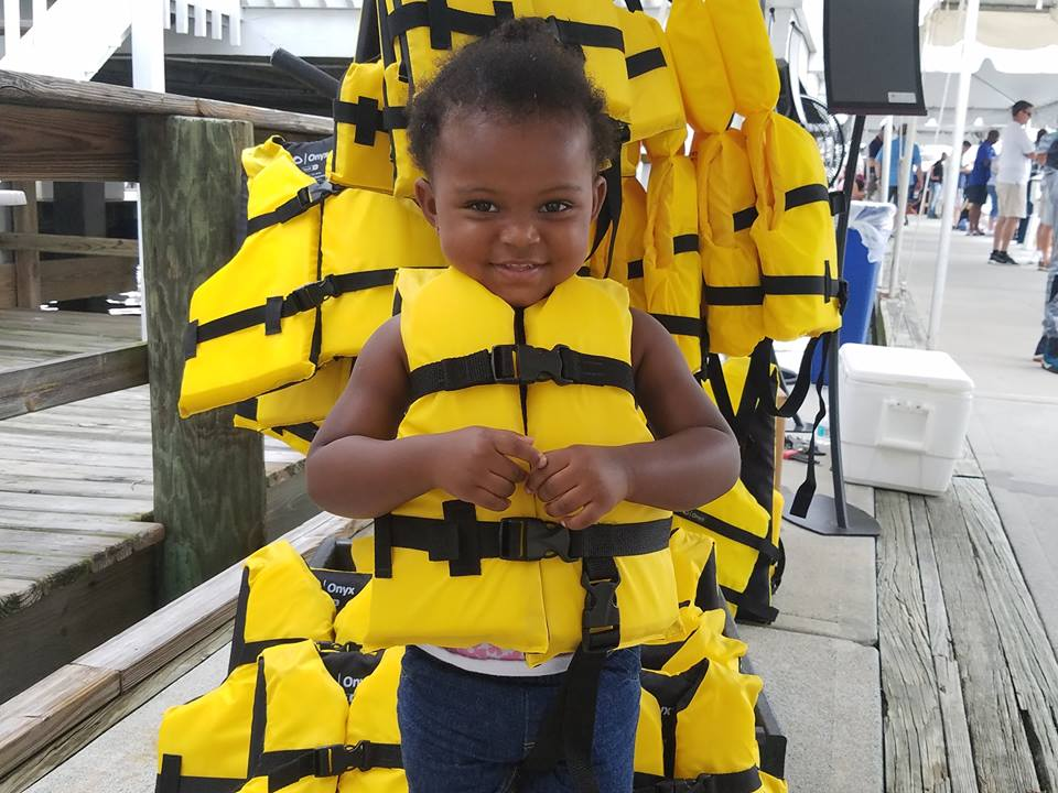 Child wearing life jacket in front of loaner stand