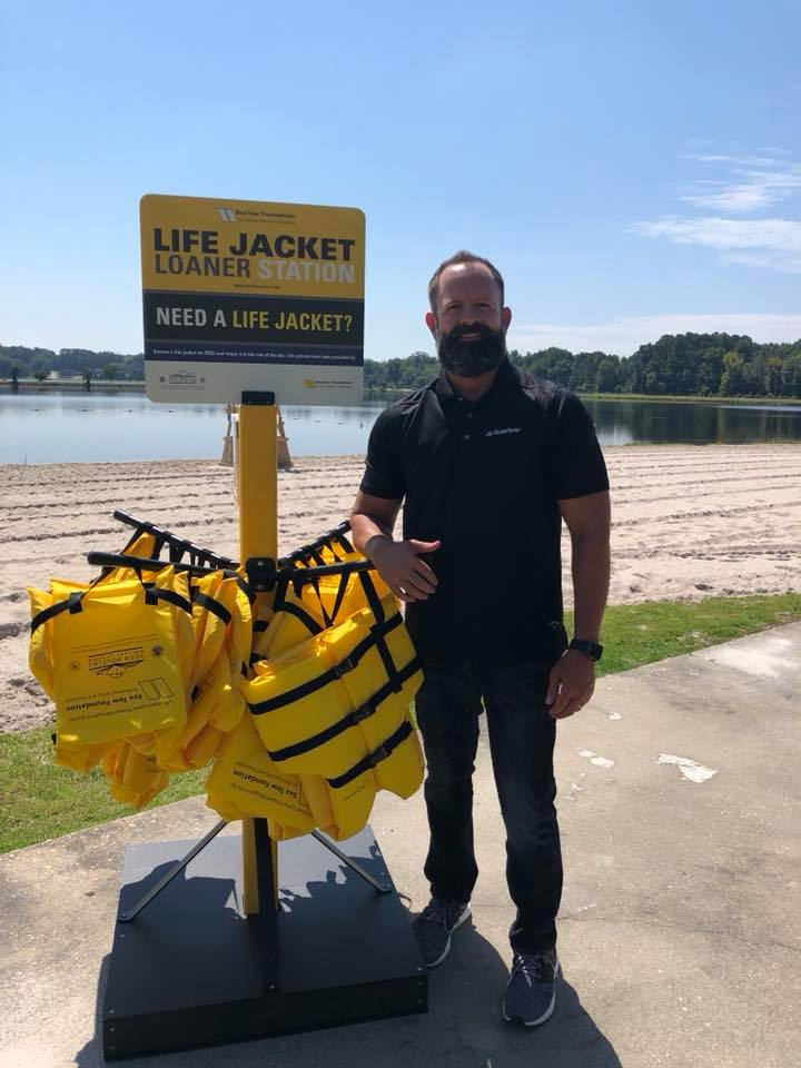 Man standing in front of life jacket loaner stand