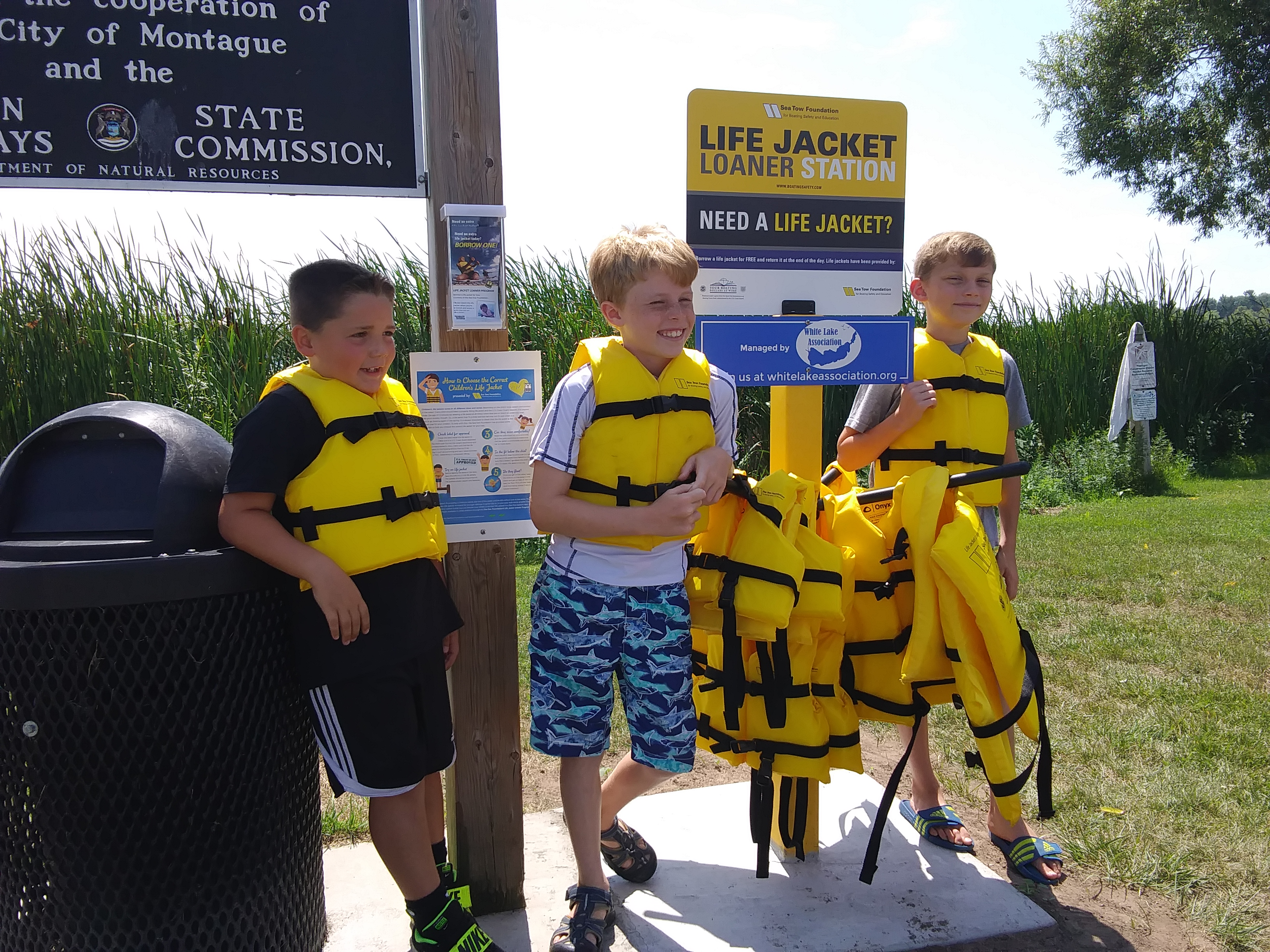 3 boys wearing life jackets in front of loaner stand