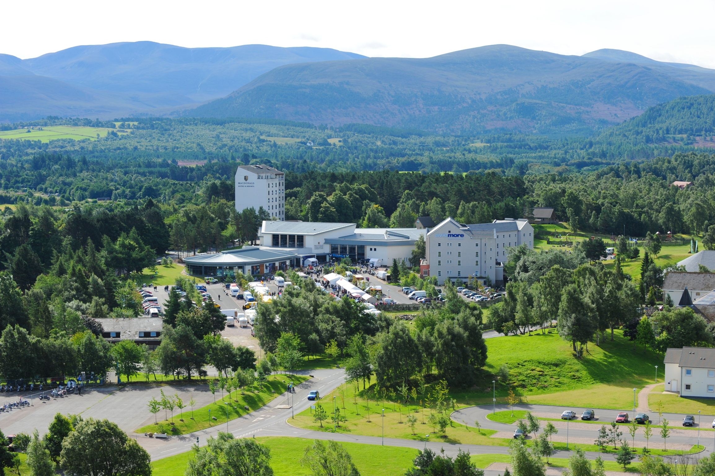 Photo of Macdonald Aviemore Resort, Cairngorms National Park, Scotland showing a white building surrounded by trees and cars