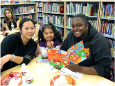 photo of adults reading with child at Oakland Public Library