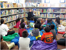 photo of Librarian reading to group of children at Oakland Public Library