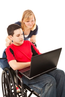Boy in Wheelchair with Computer and Adult