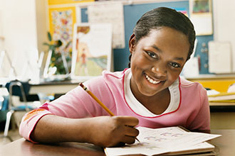 African american teen smiling at desk