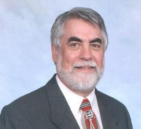 smiling white man with grey hair and beard. Wearing suit