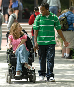 African American teen walking next to a Caucasian female in wheelchair