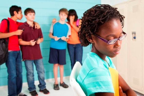 picture of black girl with glasses looking forlorn with group of middle school kids behind her