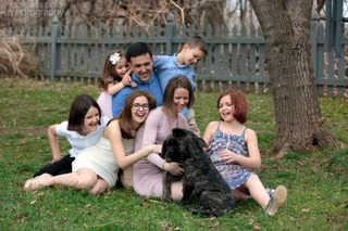 picture of family with five children, two puppies. family laughing and looking at puppies