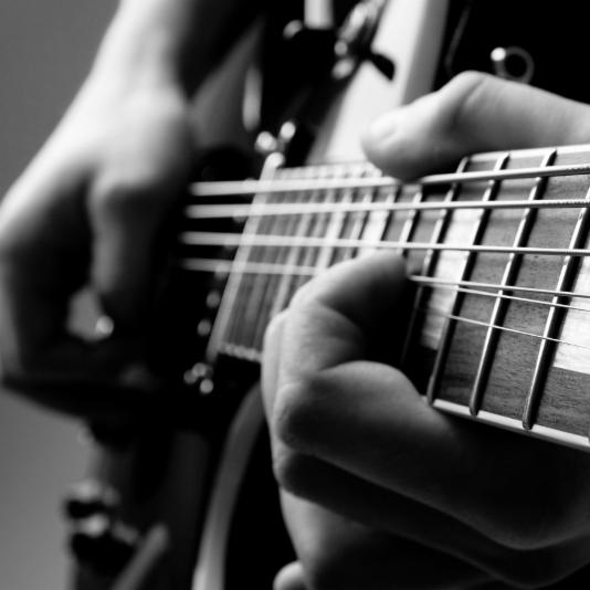 closeup of hands playing guitar