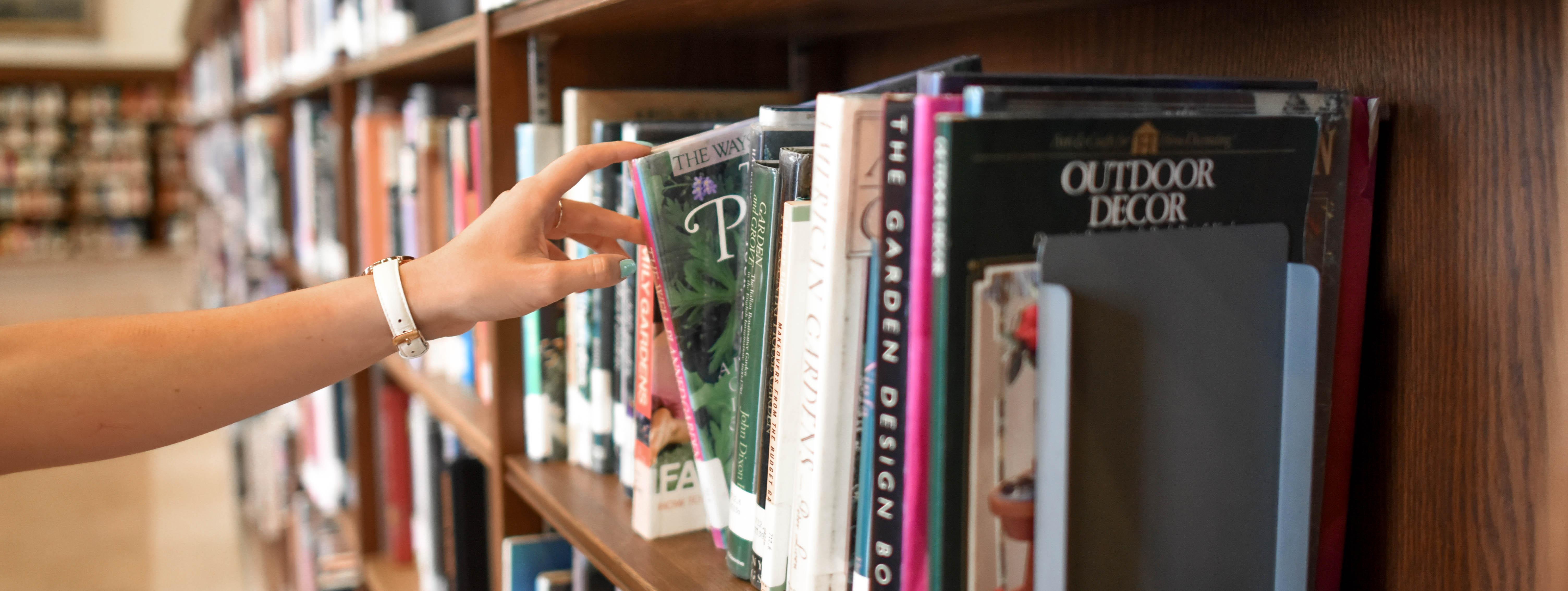 hand reaching to bookshelf