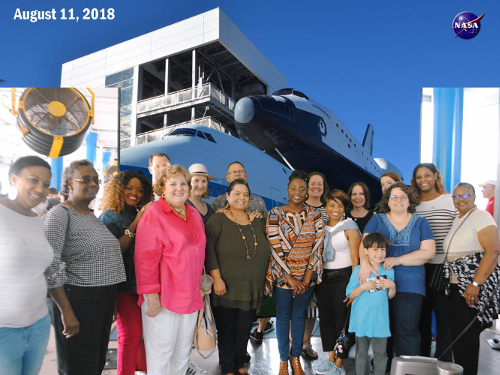 Group posing in front of space shuttle at Space Center Houston