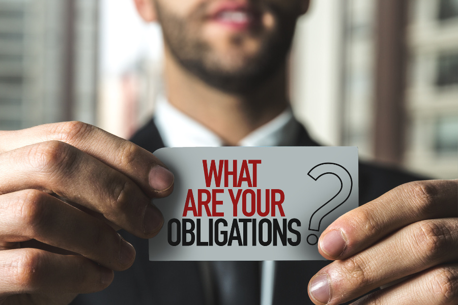 man holding a sign saying what are yur obligations