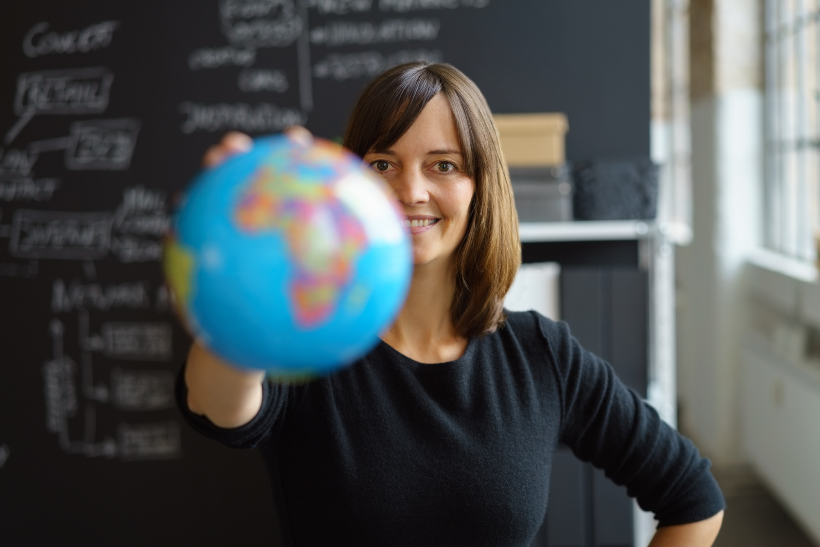 woman in a classroom holding a globe
