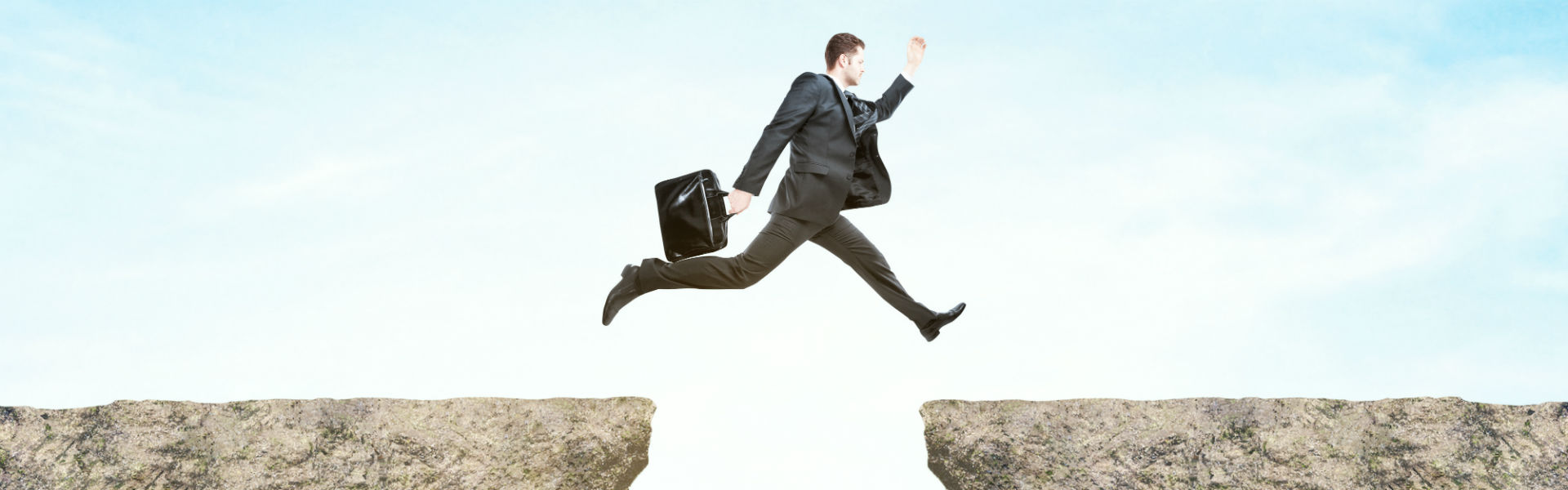 businessman jumping between cliffs