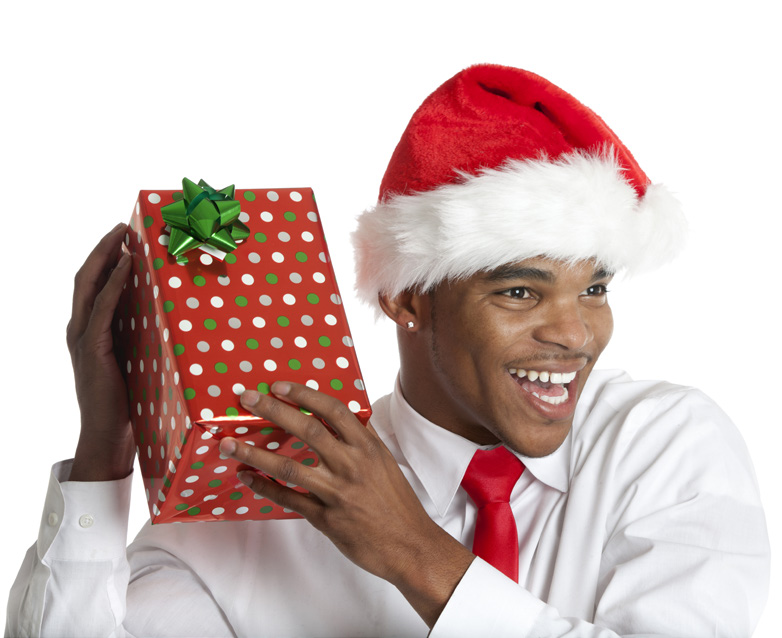 man in white dress shirt and red tie with Santa hat holding present smiling