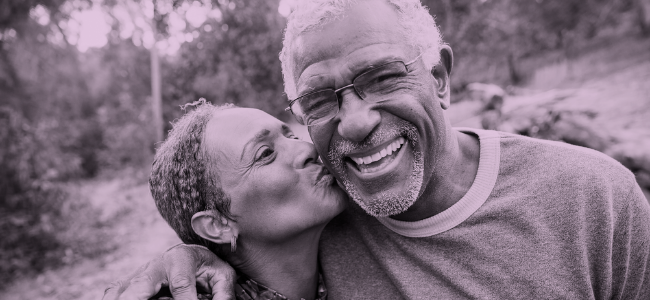 An older African American man laughs as his African American wife kisses him on the cheek.