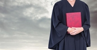 Person in robes holding red book
