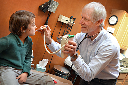 "Max Tenscher, FNP, takes the temperature of patient, Jude Comer, 8, during Jude's appointment at Integrative Primary Care Associates, LLC in Portland, Ore. on November 1, 2013. Tenscher has been the Comer family's primary care provider for the past three years and is ""like family"" to Tammy Comer, her husband and their three children."