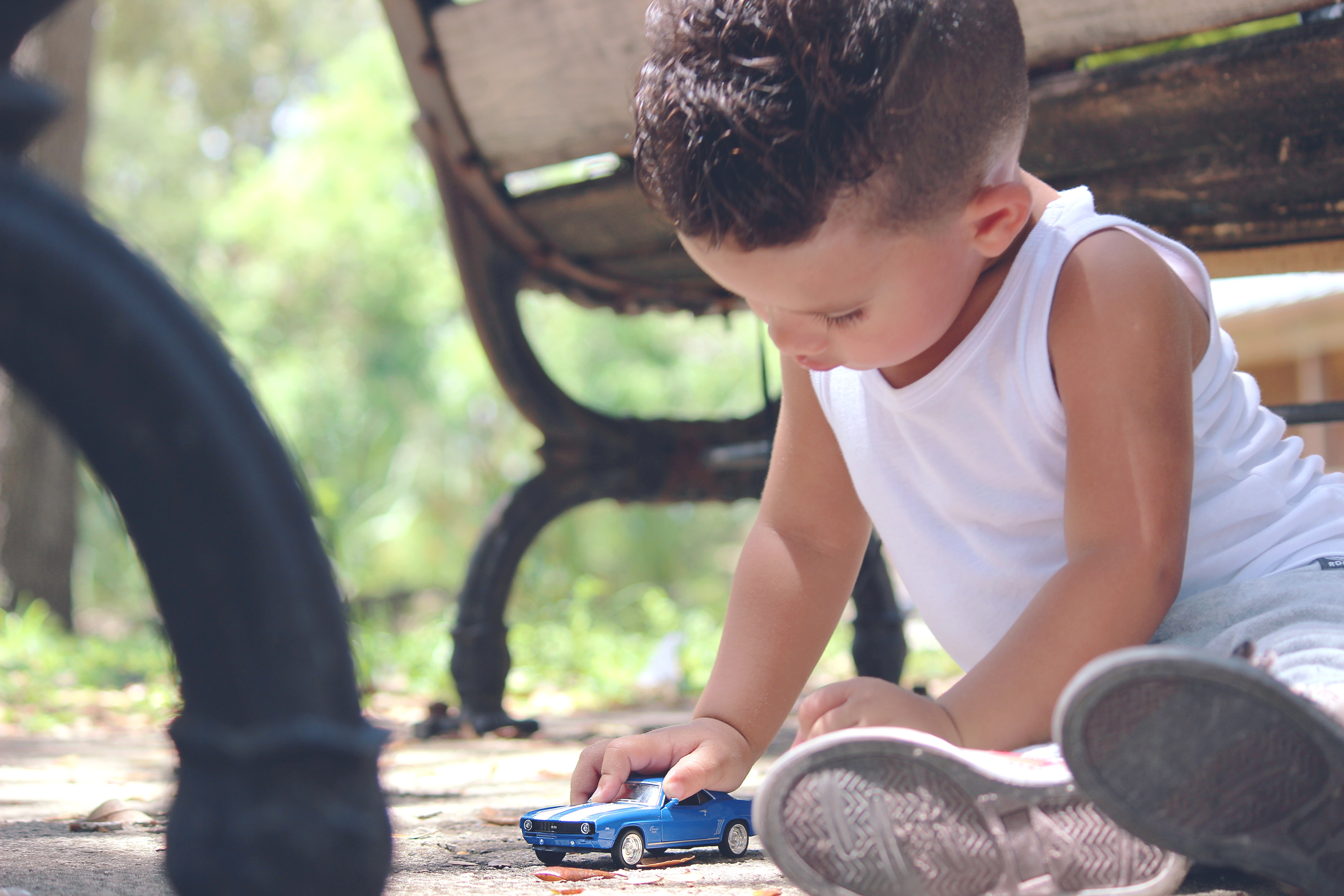 boy playing with blue toy car