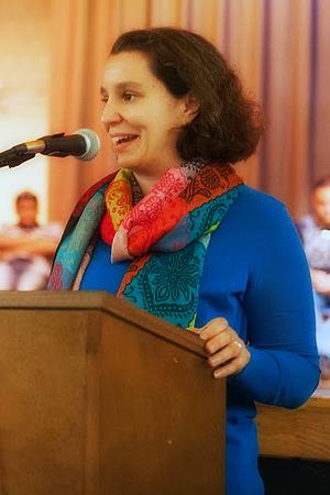 Meg Stone speaking at a podium