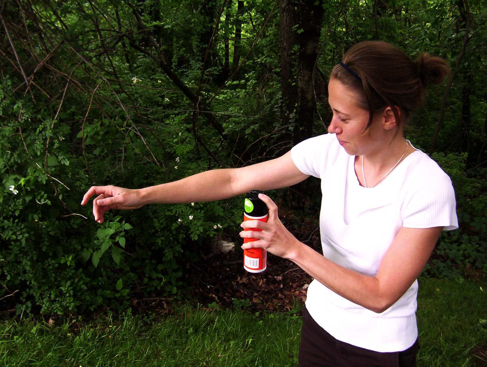Woman spraying herself with bug spray outdoors