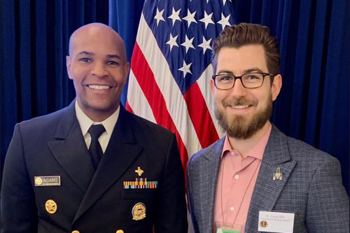 Hill presents Surgeon General Jerome Adams with a Naloxone Saves Lives pin